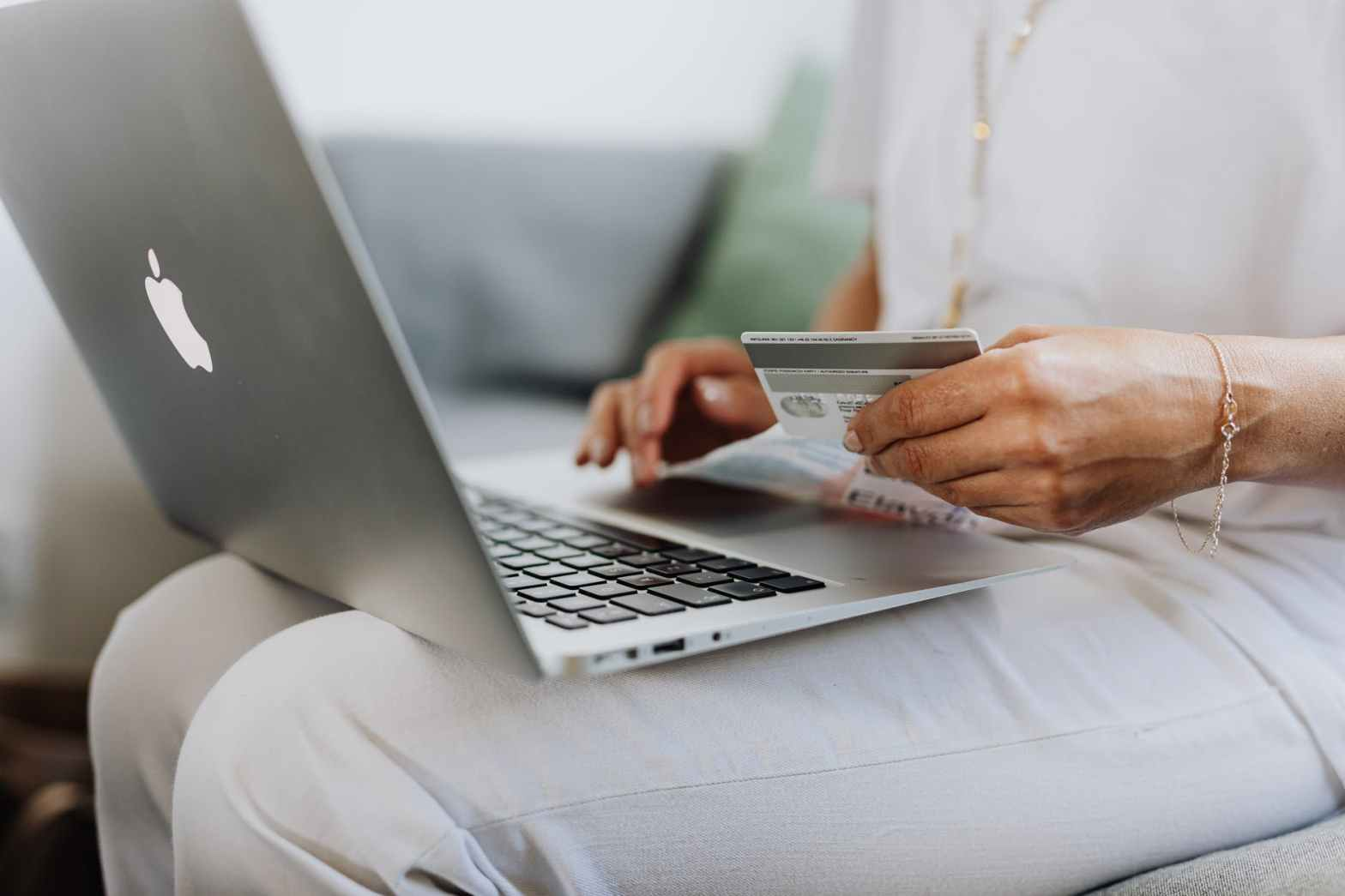 improve online sales: consumer on laptop with credit card in hand
